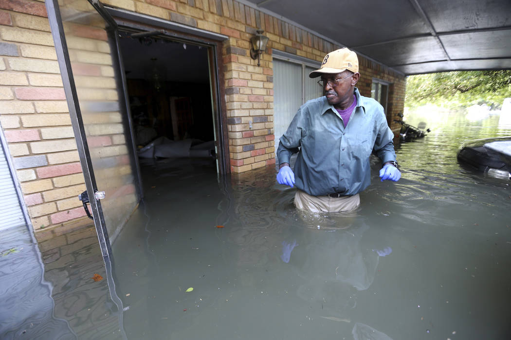 Michael Brown walks outside his flooded home, as he searches for belongings, in the aftermath of Tropical Storm Harvey, in Port Arthur, Texas, Saturday, Sept. 2, 2017. (Gerald Herbert/AP)
