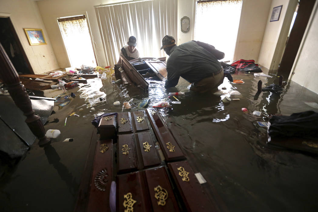 Paul England Jr., right, helps Michael Brown move bedroom furniture floating in his flooded home in the aftermath of Tropical Storm Harvey, in Port Arthur, Texas, Saturday, Sept. 2, 2017. (Gerald  ...