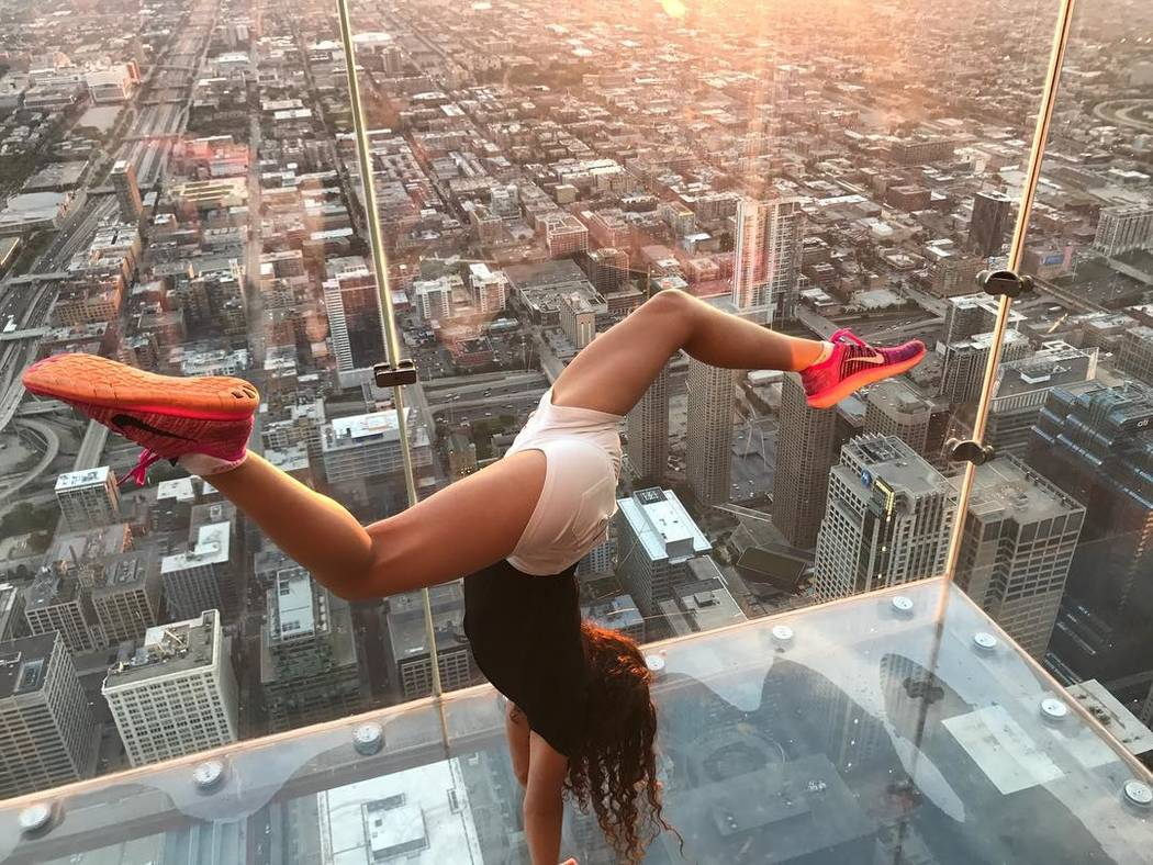 Sienna does a handstand on the Sky Deck at the 103rd floor of Willis Tower in Chicago. (Courtesy, @siennarobinson2024).