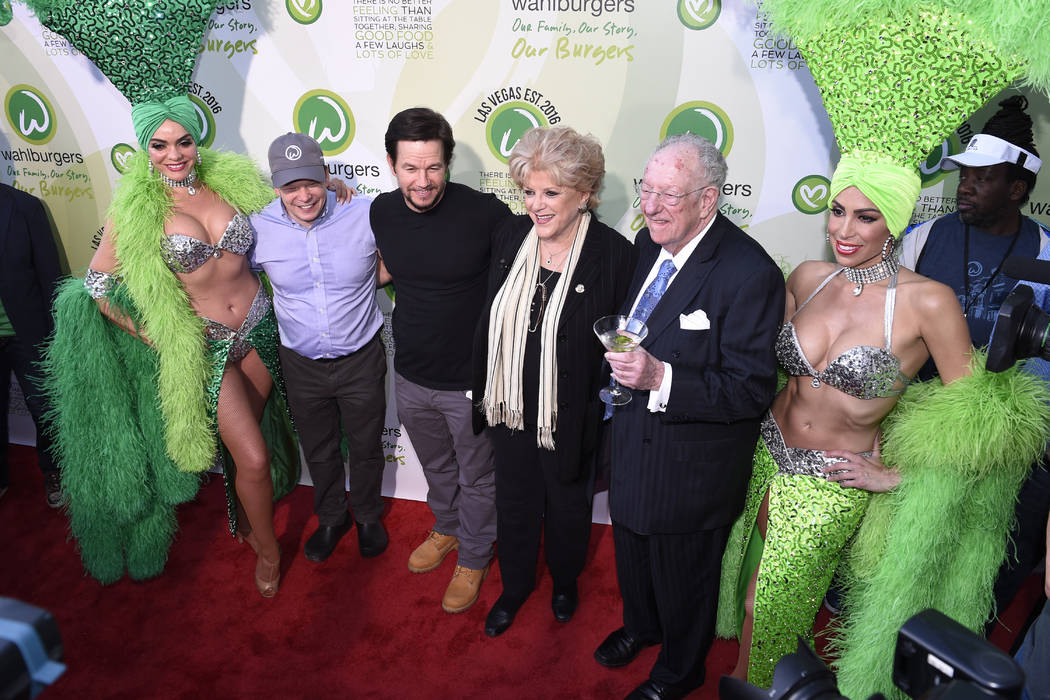 Mark Wahlberg and brother executive chef Paul Wahlberg pose with Las Vegas Mayor Carolyn Goodman and LVCVA Host Committee Chairman Oscar Goodman and showgirls as they arrive at a VIP event at Wahl ...