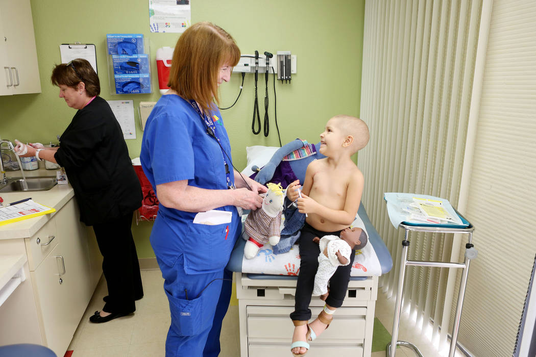 Sue Collins Waltermeyer, a child life specialist, center, talks with Leukemia patient Madilyn Cash, 4, while Nurse Practitioner Arlene Bayreder working at the Children's Specialty Center of Nevada ...