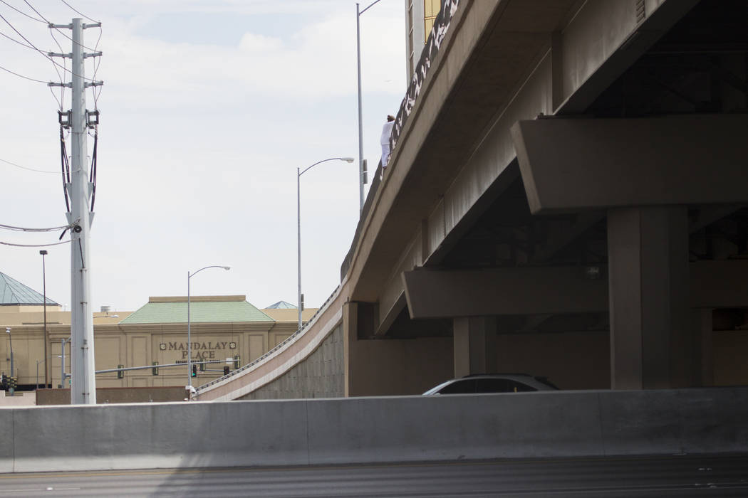 A person hangs off the Hacienda Avenue overpass and above the I-15 northbound lanes in Las Vegas, on Monday, Sept. 4, 2017. The person was rescued by Clark County Fire Department using a fire engi ...