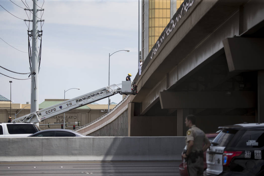 A person hanging off the Hacienda Avenue overpass and above the I-15 northbound lanes is rescued by the Clark County Fire Department in Las Vegas, on Monday, Sept. 4, 2017. Erik Verduzco Las Vegas ...