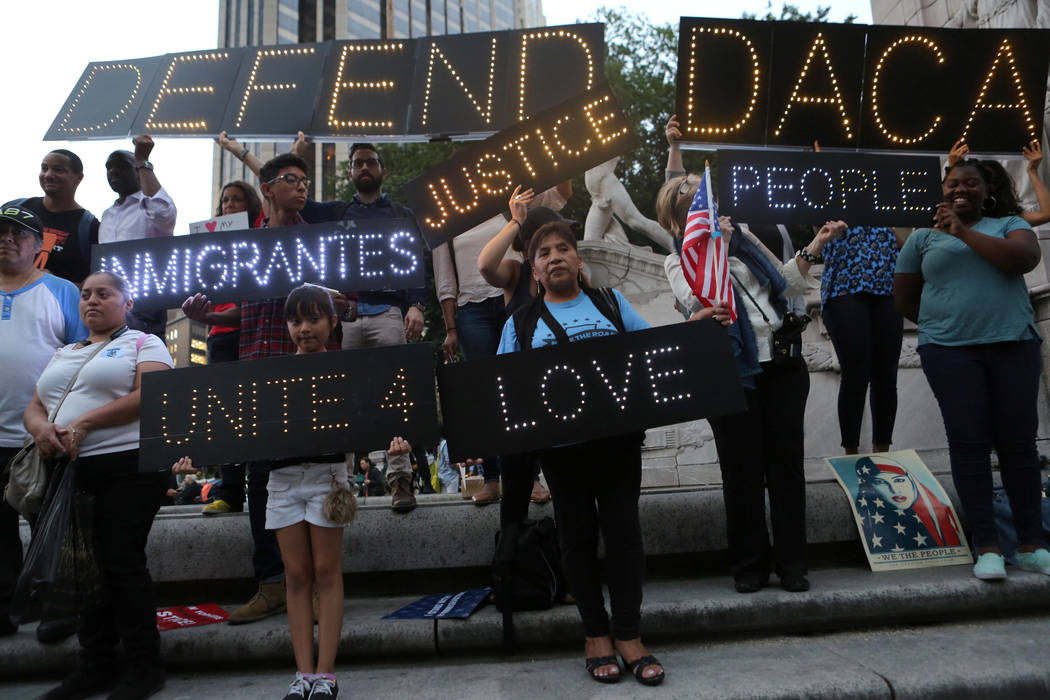 People hold signs against President Donald Trump's proposed end of the DACA program that protects immigrant children from deportation at a protest in New York on August 30, 2017. (REUTERS/Joe Penney)
