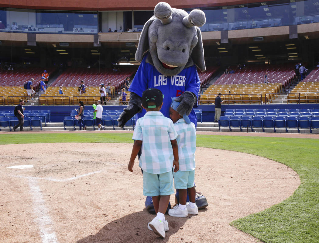 Jerimiah, 4 1/2 , left, and Scott, 3, right, who only gave their first names, hug Cosmo the alien after running bases after the last game of the Las Vegas 51s season at Cashman Field in Las Vegas, ...