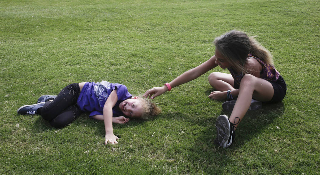 Gianna Gibson, 6, left, and  Kamryn Gibson, 11, right, both of East Las Vegas, giggle after rolling down a hill near Cashman Field after  the last game of the Las Vegas 51s season at Cashman Field ...