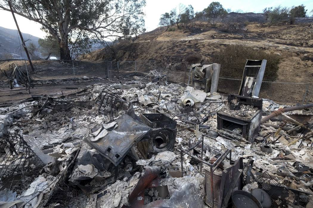 The charred remains of a burned out home are seen Monday, Sept. 4, 2017, in the Sunland-Tujunga section of Los Angeles. Wildfires forced thousands to flee their homes across the U.S. West during a ...