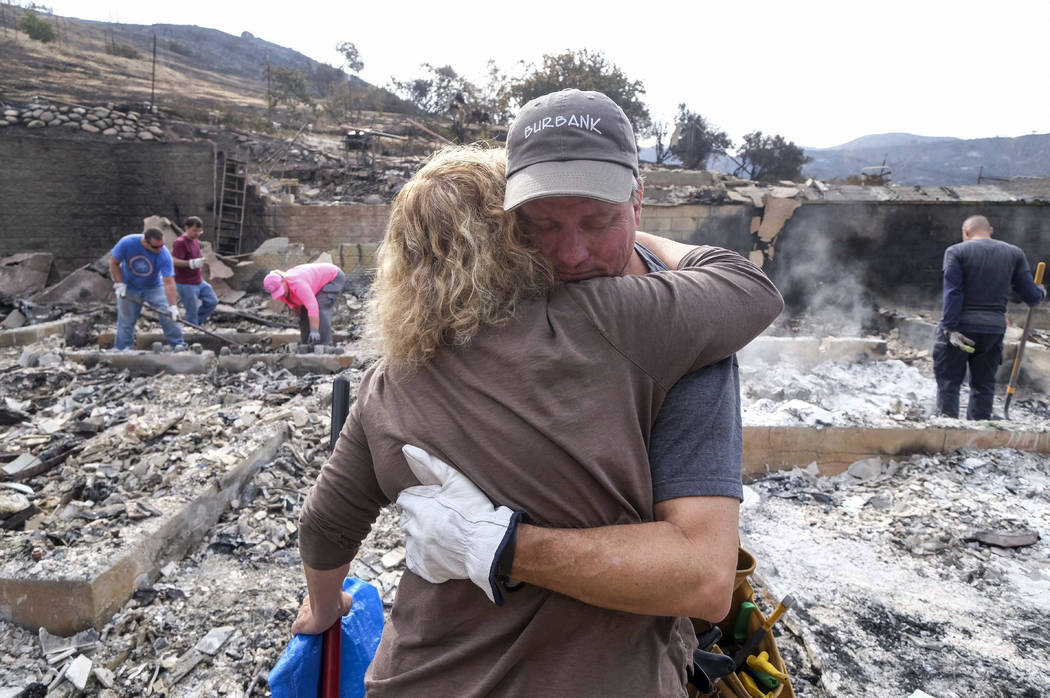 Craig Bolleson hugs his friend in his burned out home, Monday, Sept. 4, 2017, in the Sunland-Tujunga section of Los Angeles. Wildfires forced thousands to flee their homes across the U.S. West dur ...