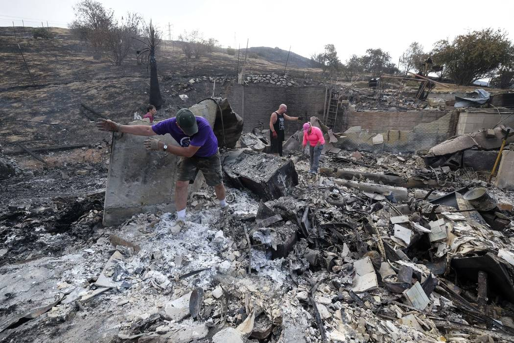 Friends of the home owner survey the charred debris left in a burned out home, Monday, Sept. 4, 2017, in the Sunland-Tujunga section of Los Angeles. Wildfires forced thousands to flee their homes  ...