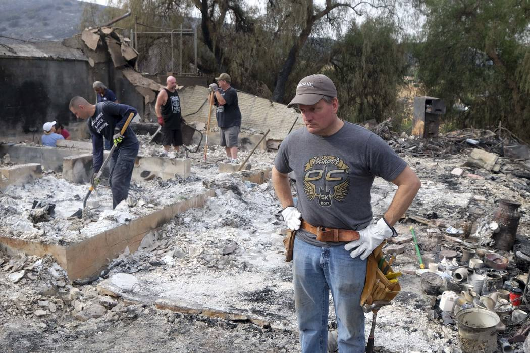 Home owner Craig Bolleson surveys the charred debris left in his burned out home, Monday, Sept. 4, 2017, in the Sunland-Tujunga section of Los Angeles. Wildfires forced thousands to flee their hom ...