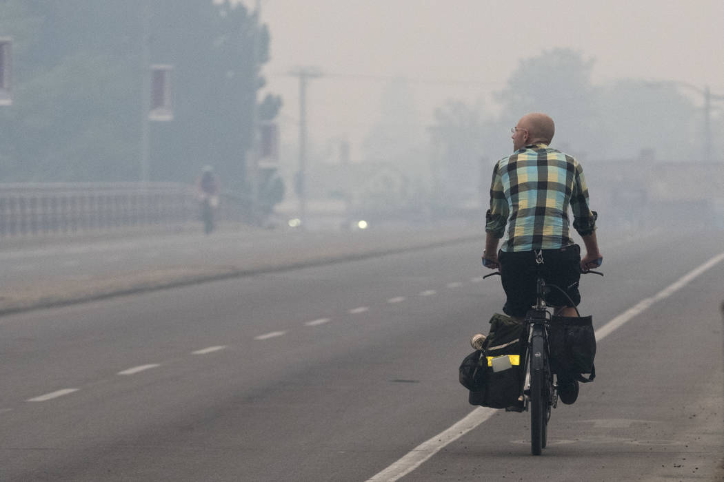 A bicyclist makes his way down Higgins Avenue in Missoula, Mont. as smoke from the nearby Lolo Peak Fire fills the air on Monday, Sept. 4, 2017. The air quality is has been measured at hazardous b ...