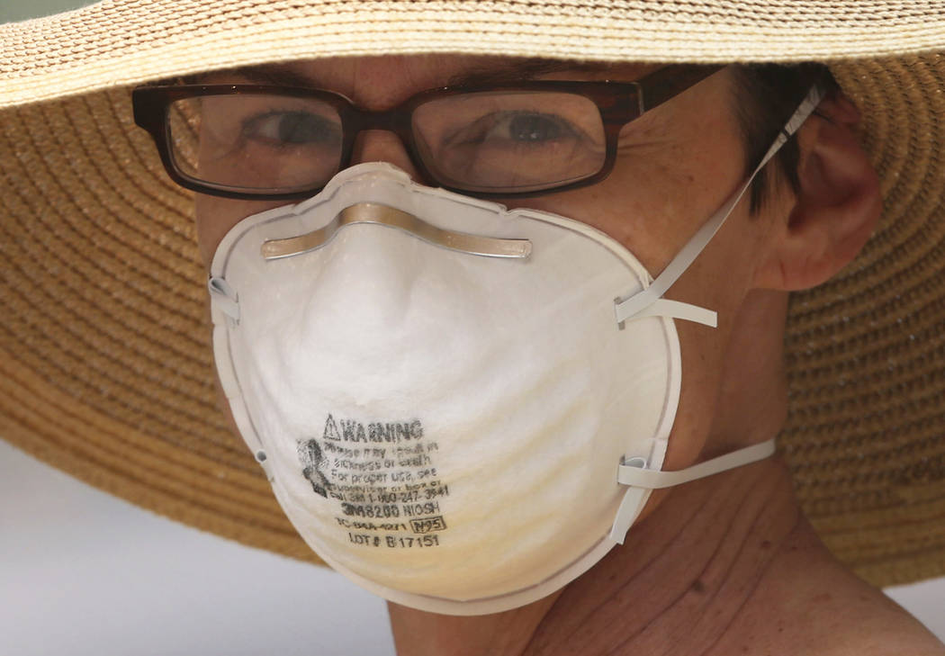 Kate Kevern guards from dangerous smoke with a mask rated for construction work as she walks home through downtown Eugene, Ore. Monday, Sept. 4, 2017. (Chris Pietsch/The Register-Guard via AP Photo)