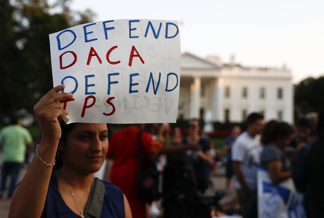 "A woman holds up a sign that reads ""Defend DACA Defend TPS"" during a rally supporting Deferred Action for Childhood Arrivals, or DACA, outside the White House in Washington, Mond ..."