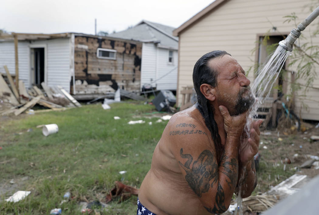 In this Sept. 2, 2017, photo, Bob Campbell baths outdoors using a makeshift shower he attached to a garden hose, in Port Aransas, Texas. Rockport and Port Aransas bore the brunt of one of the stro ...