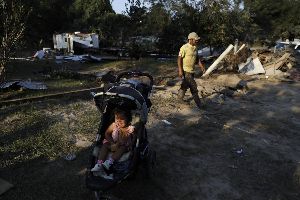 Melisa Vasquez cries in a stroller as her father Ervin Vasquez passes while the family digs out from the destruction left when floodwaters from Harvey swept through their mobile homes Monday, Sept ...