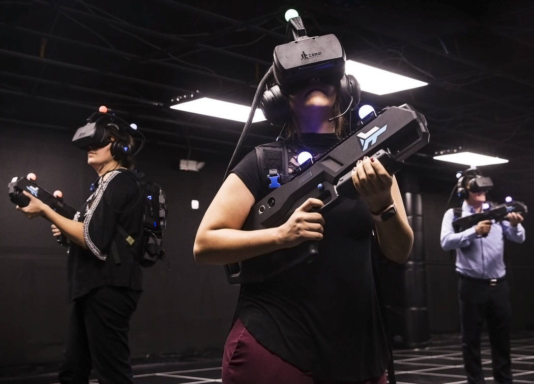 "Leticia Carrillo, left, Joslyn Garcia and Matt Pinal are geared up to play ""Zombie Survival"" in the 2000 square foot, virtual reality gaming arena at Level Up on Tuesday, Septemb ..."