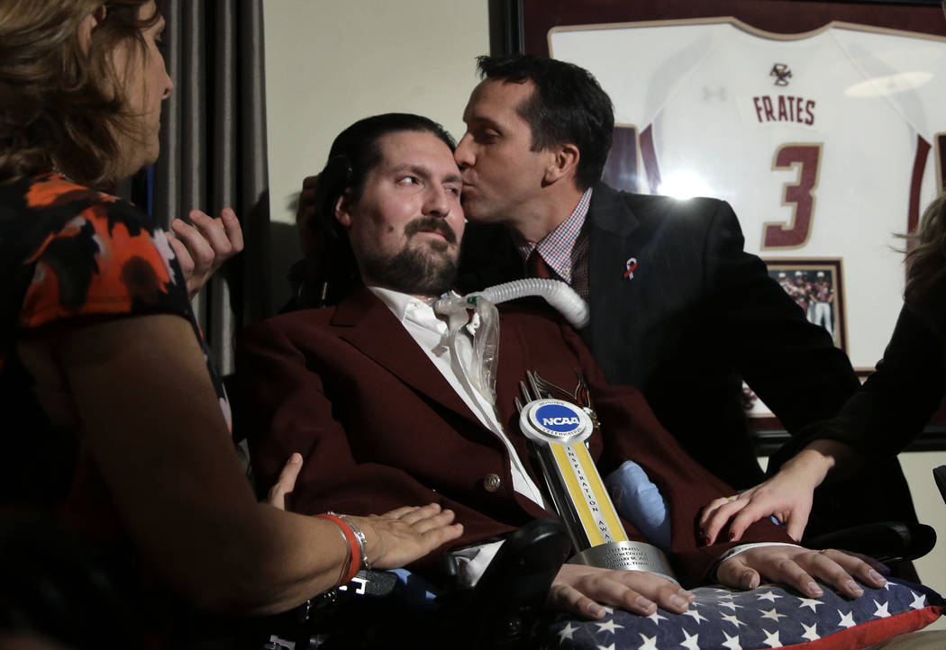 FILE - In this Dec. 13, 2016, file photo, former Boston College baseball captain Pete Frates, center left, receives a kiss from Boston College head baseball coach Mike Gambino after Frates was pre ...
