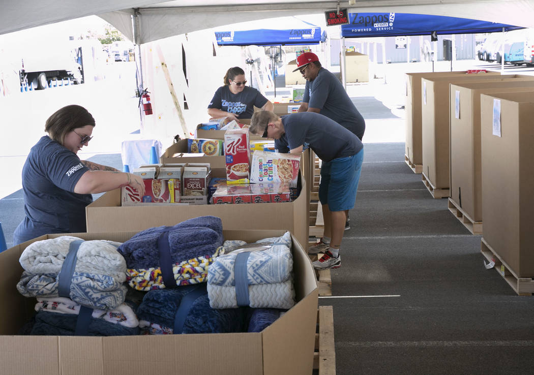 Zappos employees, including Precious Bucher, left, Cody Britton, right, and Andre Narcesse, second right, sort out donations in downtown Las Vegas for survivors of Hurricane Harvey on Tuesday, Sep ...