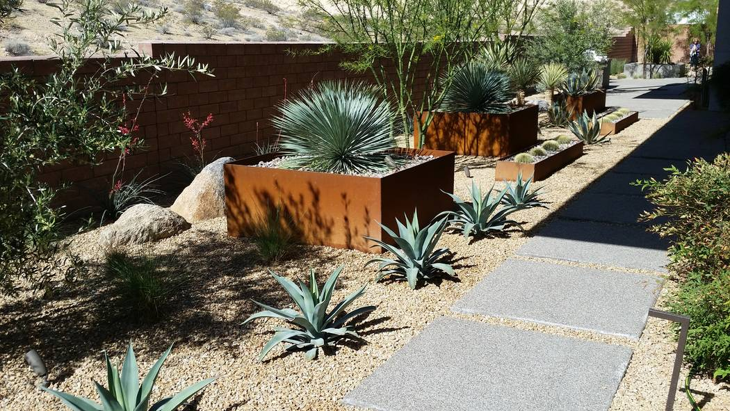 Sage Design Studios Metal plant boxes add a decorative look to this rock and stone landscape.
