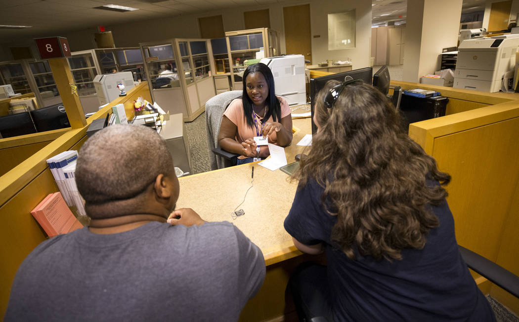 Deputy Assessor Tamicka Washington, center, helps Stephanie and Colton Freeman with a transaction at the Clark County Assessor's office in Las Vegas on Friday, Sept. 8, 2017. Richard Brian Las Veg ...