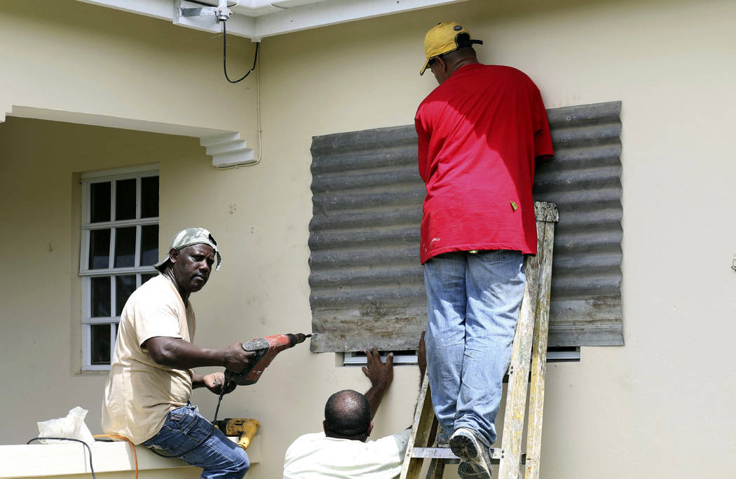 People put up a steel sheet over a window in preparation for Hurricane Irma, in Fort Road, St. John's, Antigua and Barbuda, Tuesday, Sept. 5, 2017.  Irma grew into a dangerous Category 5 storm, th ...
