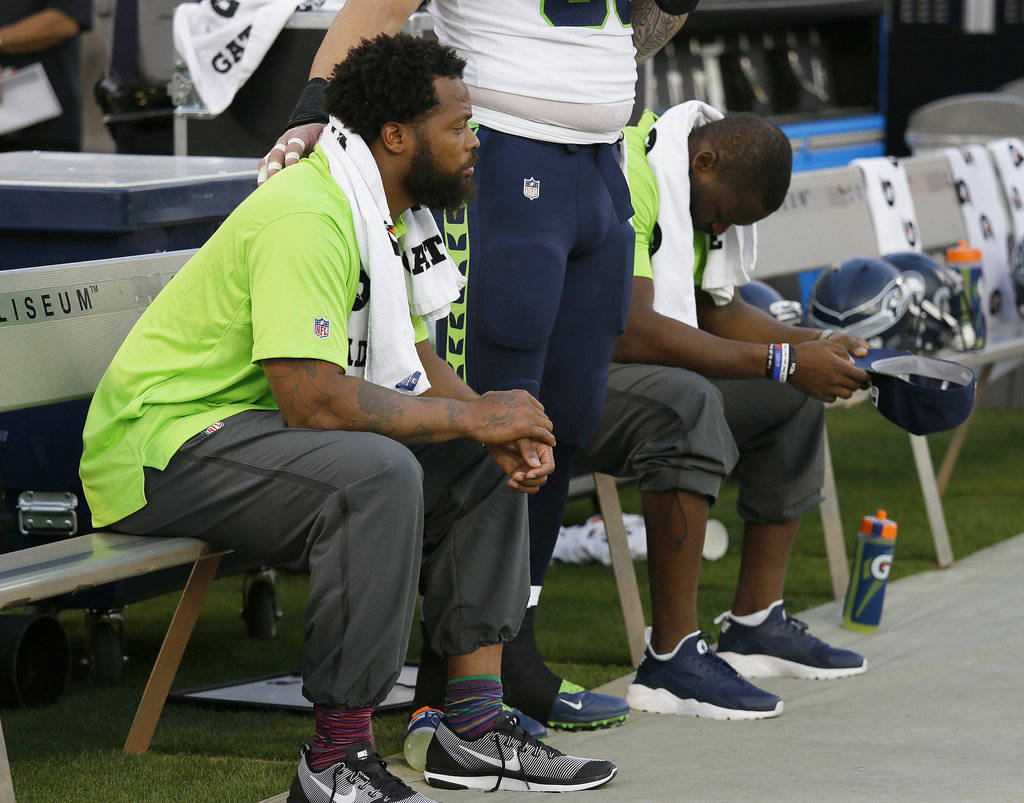 FILE - This Thursday, Aug. 31, 2017 file photo Seattle Seahawks defensive end Michael Bennett, left, sits during the playing of the national anthem next to Justin Britt, center, and another teamma ...