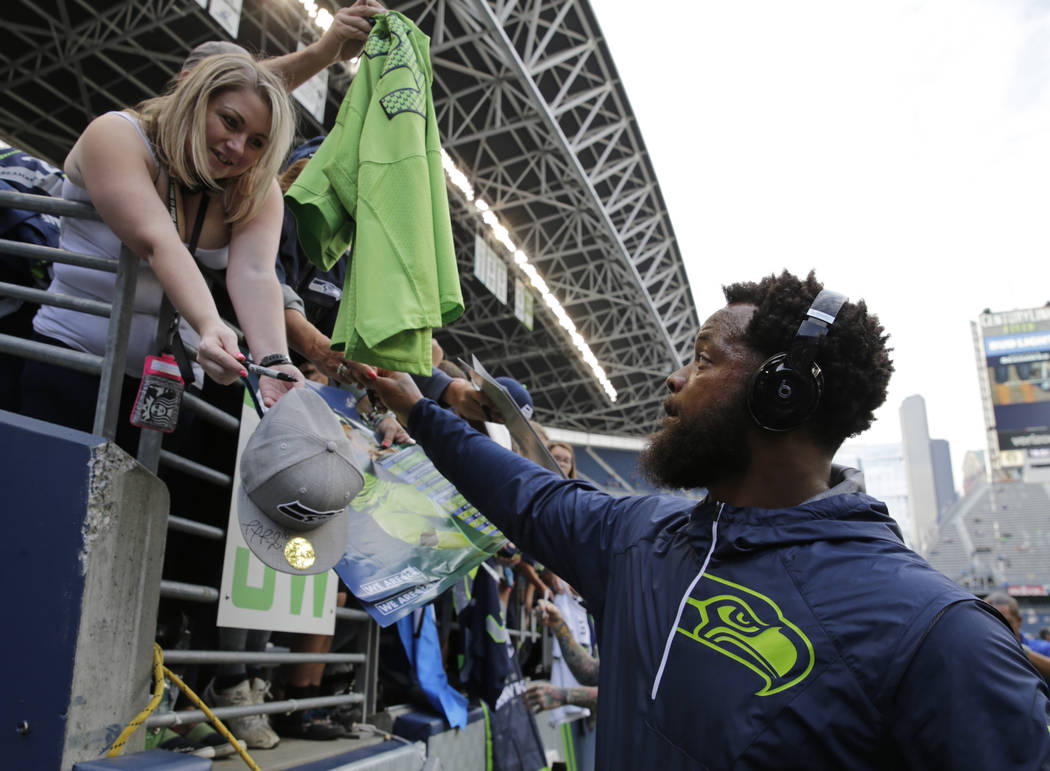 Seattle Seahawks defensive end Michael Bennett signs autographs for fans before the team's NFL football preseason game against the Minnesota Vikings, Friday, Aug. 18, 2017, in Seattle. (Stephen Br ...