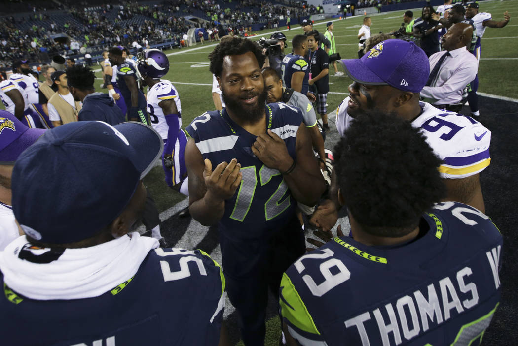 Seattle Seahawks defensive end Michael Bennett, center talks with teammate Earl Thomas and Minnesota Vikings' Everson Griffen, upper right, following an NFL football preseason game, Friday, Aug. 1 ...