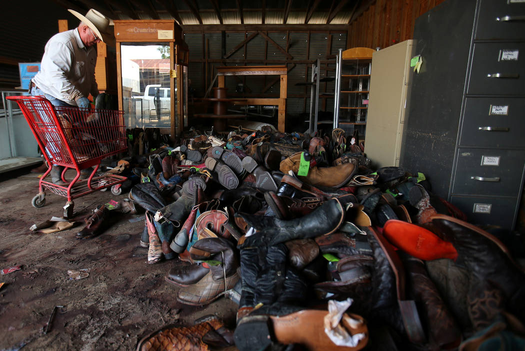 Tommy Phillips helps his son's small business TNT Western Wear as he sorts flood damaged cowboy boots in the aftermath of tropical storm Harvey in Wharton, Texas, U.S., September 6, 2017. REUTERS/ ...