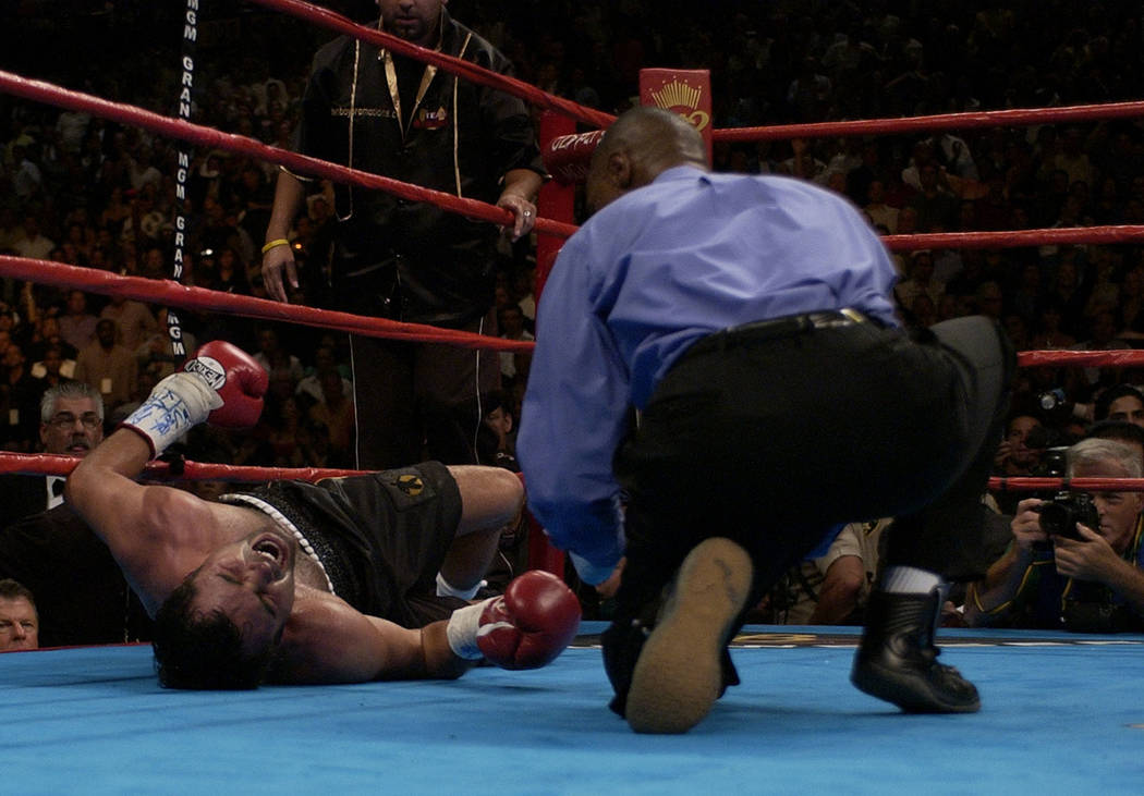 Referee Kenny Bayless leans over Oscar De La Hoya, of Los Angeles, as he writhes on the mat after taking a body shot from Bernard Hopkins, of Philadelphia, at 1:38 of the ninth round during their  ...