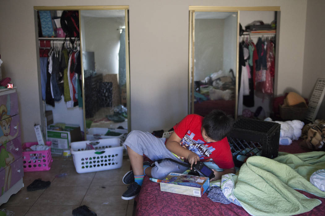Ivan Meneses plays with his camera at his home in Las Vegas, Thursday, Aug. 10, 2017. Meneses' mother fears that a change in current health care laws will take away access to Medicaid for herself  ...