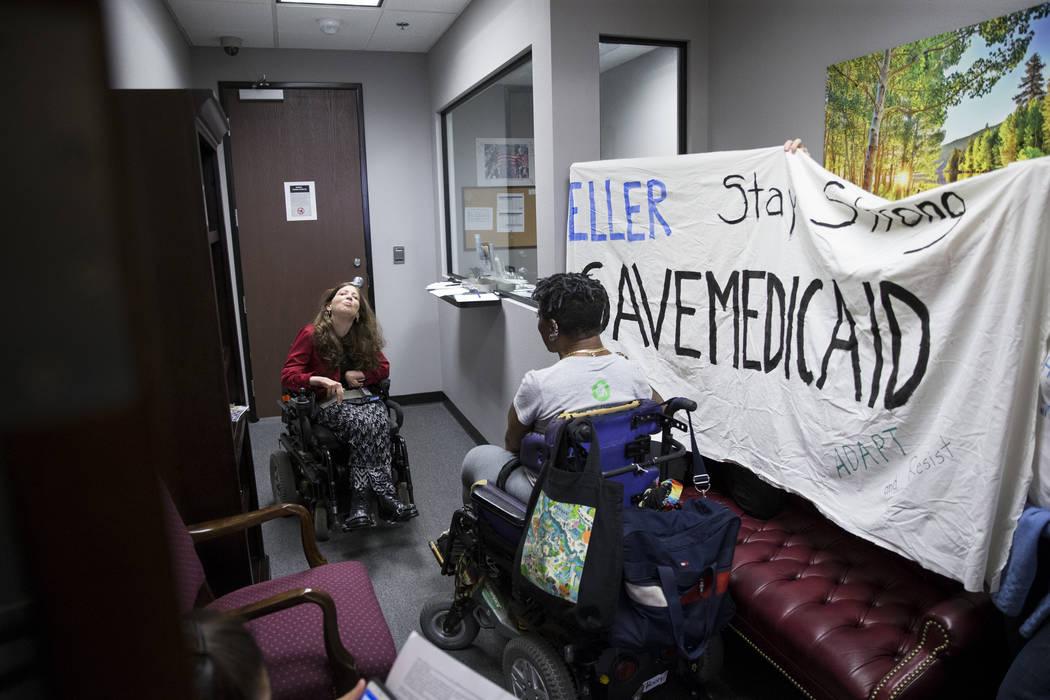 Sascha Bittner, left, and Monique Harris, demonstrate in support of the Medicaid program inside the office of Sen. Dean Heller, R-Nev., in Las Vegas, on Thursday, July 20, 2017. Erik Verduzco Las  ...