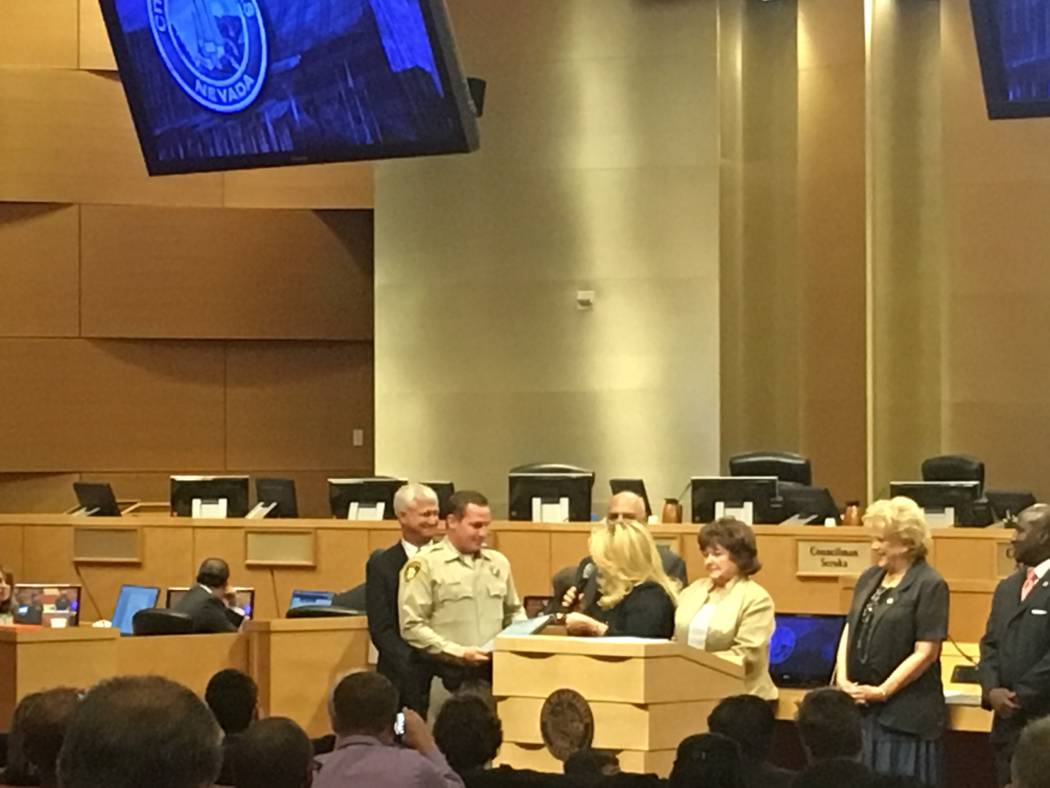 Officer Jeffrey Burr receives his Citizen of the Month plaque from city councilwoman Michele Fiore at the Las Vegas city council meeting on September 6, 2017. (Katelyn Umholtz/Las Vegas Review-Jou ...