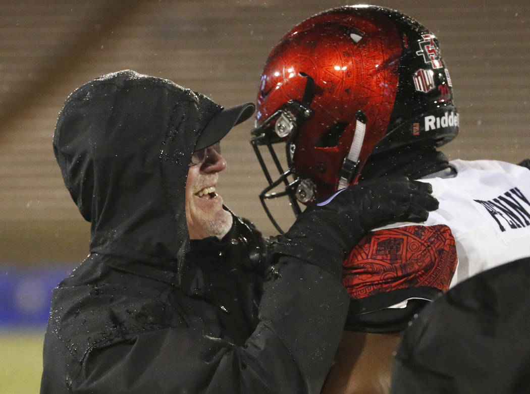 San Diego State head coach Rocky Long, left, smiles as he hugs running back Rashaad Penny (20) after Penny scored a touchdown against Air Force during an NCAA college football game, Saturday, Sept ...