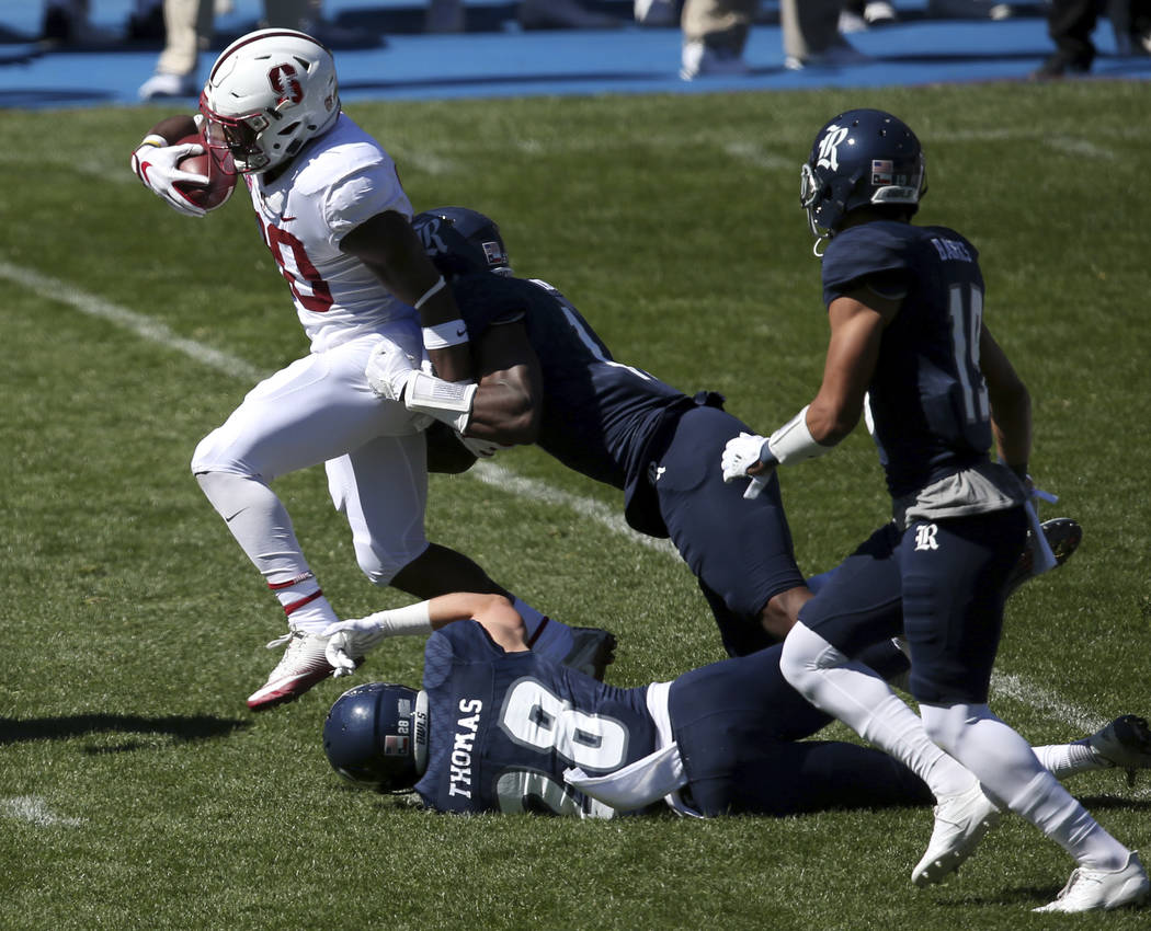 Stanford's running back Bryce Love, left, breaks tackles as he runs against the Rice defence during the opening game of the U.S. college football season in Sydney, Sunday Aug. 27, 2017. (AP Photo/ ...