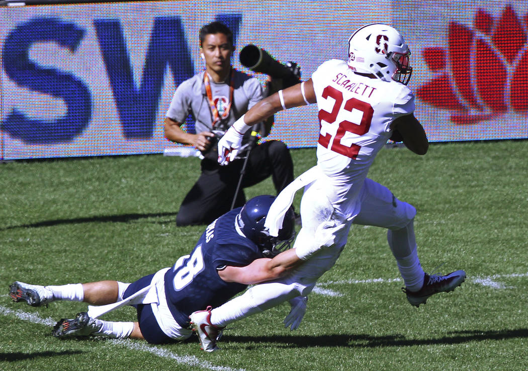 Stanford's running back Cameron Scarlett, right, breaks the tackle from Rice's safety Cole Thomas during the opening game of the U.S. college football season in Sydney, Sunday, Aug. 27, 2017. (AP  ...
