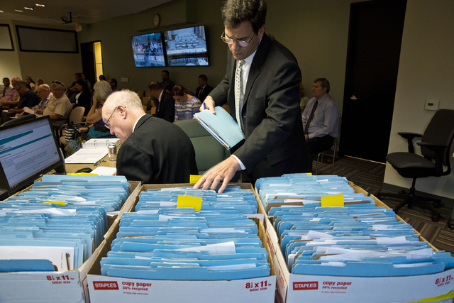 Director of investigations Paul Rozario searches through files pertaining to Summerlin Energy's bankruptcy during a meeting of the Nevada State Contractors Board at their offices in Henderson on T ...