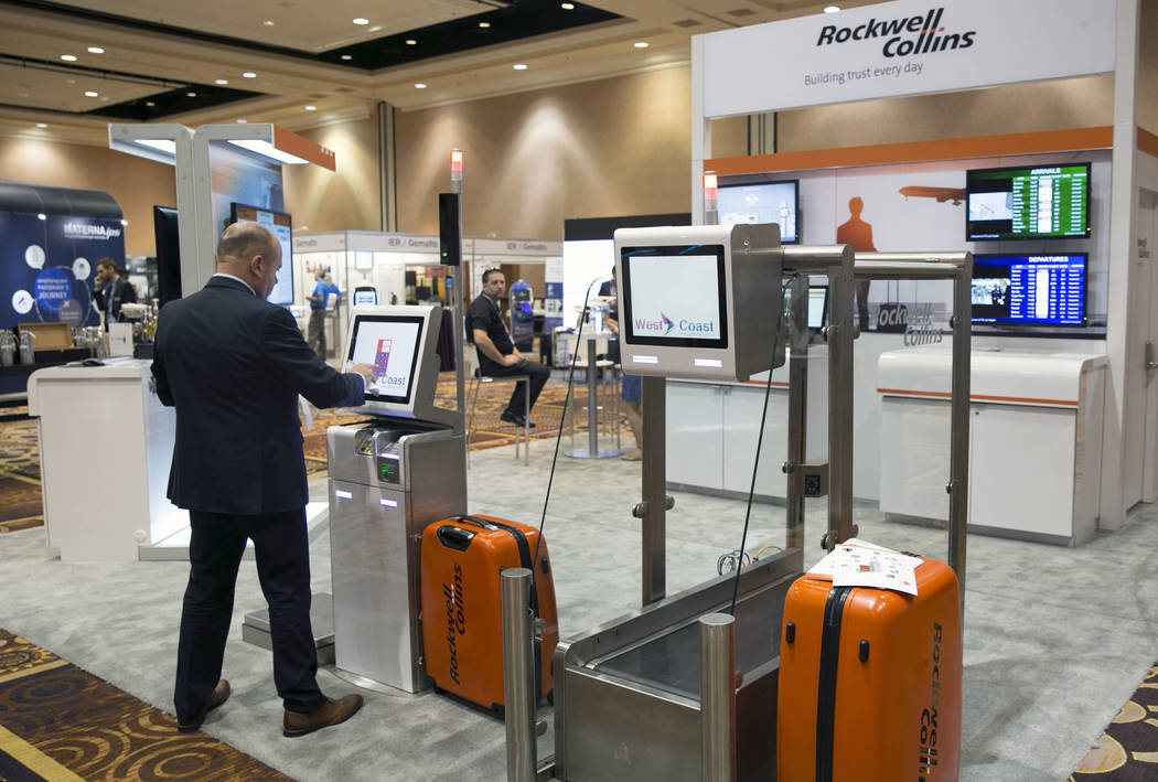 Robin Springer, global product manager at Rockwell Collins, demonstrates how to check-in a luggage at self-service baggage check-in kiosk during the Future Travel Experience expo at the Mandalay B ...