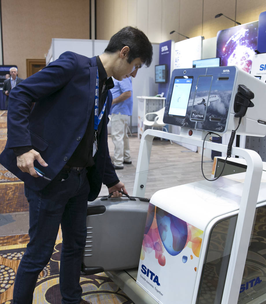 Carlos Sevciuc demonstrates how to check-in a luggage at SITA's self-service baggage check-in kiosk during the Future Travel Experience expo at the Mandalay Bay on Friday, Sept. 8, 2017, in Las Ve ...