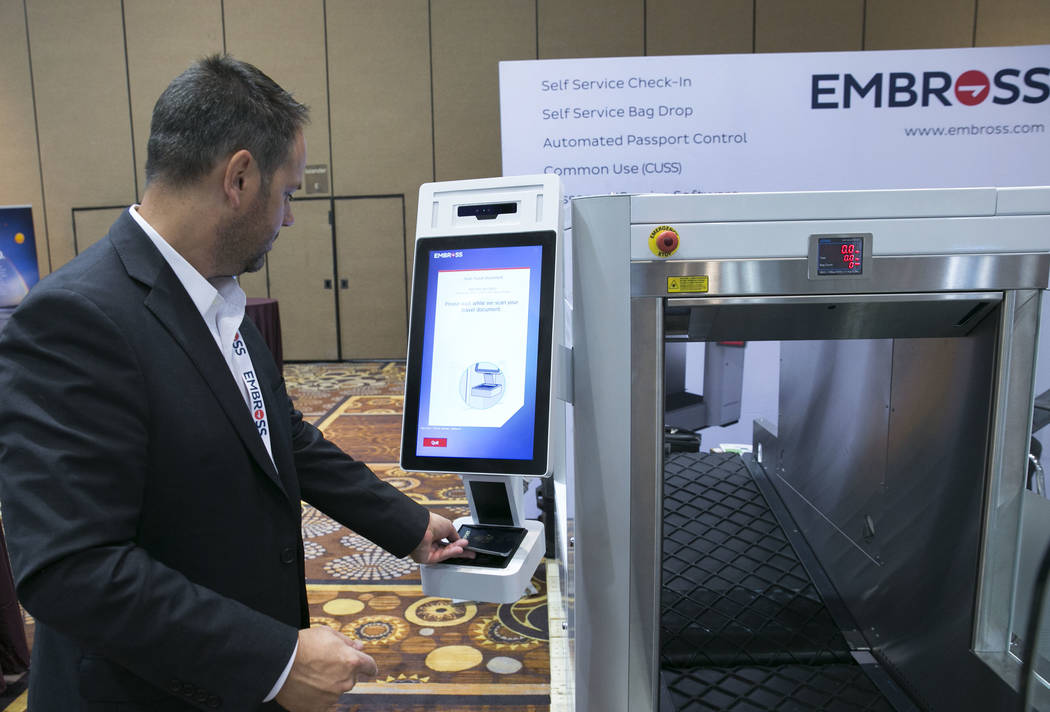 Brad Iverson, vice president global sales and marketing at Embross, demonstrates how to scan a passport at Embross' automated passport control kiosk during the Future Travel Experience expo at the ...