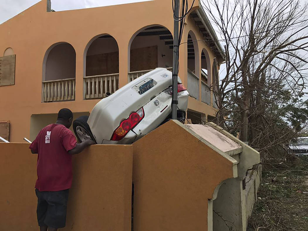 In this Wednesday, Sept. 6, 2017 photo, a man looks at a vehicle turned upside down by winds brought on by Hurricane Irma in the British overseas territory of Anguilla. Irma scraped Cuba's norther ...