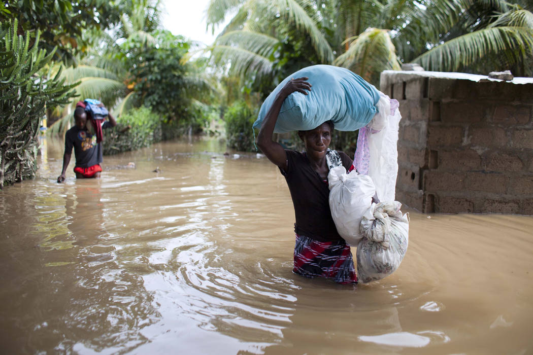 Assilia Joseph, right, and her son Wisner Jean Baptiste, carry their belongings they salvaged from their flooded home after the passing of Hurricane Irma, in Fort-Liberte, Haiti, Friday Sept. 8, 2 ...