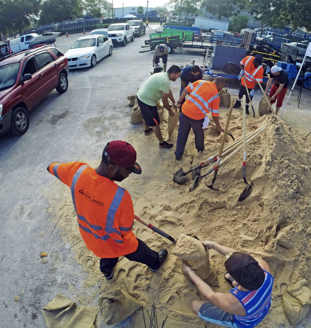 Residents fill up sandbags Thursday, Sept. 7, 2017, in Orlando, Fla., as they prepare for Hurricane Irma. Long lines of vehicles waited for hours to get a 10 sandbag limit at the City of Orlando P ...