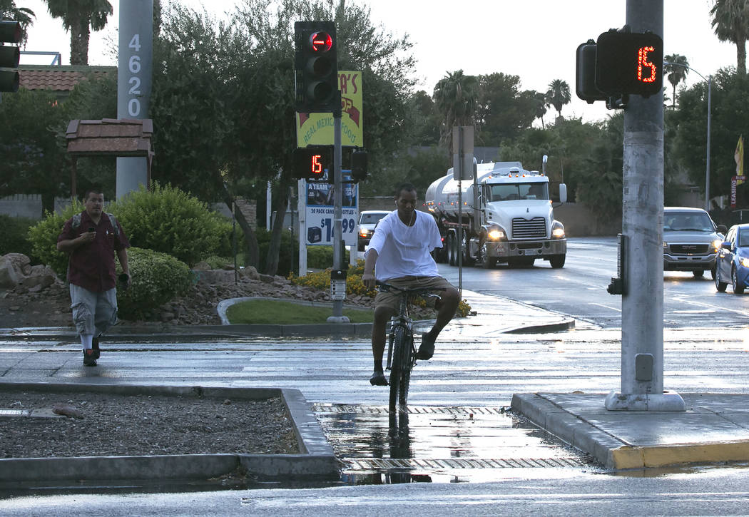 A pedestrian and a bicyclist cross Boulder Highway as light rain falls in Las Vegas on Friday, Sept. 8, 2017. (Bizuayehu Tesfaye/Las Vegas Review-Journal) @bizutesfaye