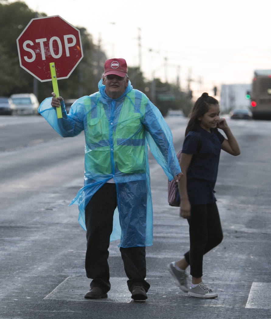 Crossing guard Robert Lavely assists a student across the street at the intersection of Parkdale Avenue and Vegas Valley Drive as lite rain falls in Las Vegas on Friday, Sept. 8, 2017. (Bizuayehu  ...