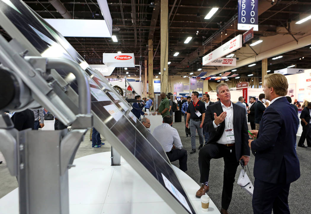 Enmax's director of operations Jason Atkinson, left, and Jinko Solar sales manager M. Ryan Manchee discuss Jinko solar panels during the Solar Power International 2017 at the Mandalay Bay Conventi ...