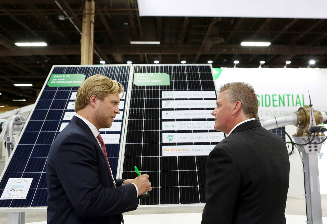Jinko Solar sales manager M. Ryan Manchee, left, and Enmax's director of operations Jason Atkinson discuss Jinko solar panels during the Solar Power International 2017 at the Mandalay Bay Conventi ...
