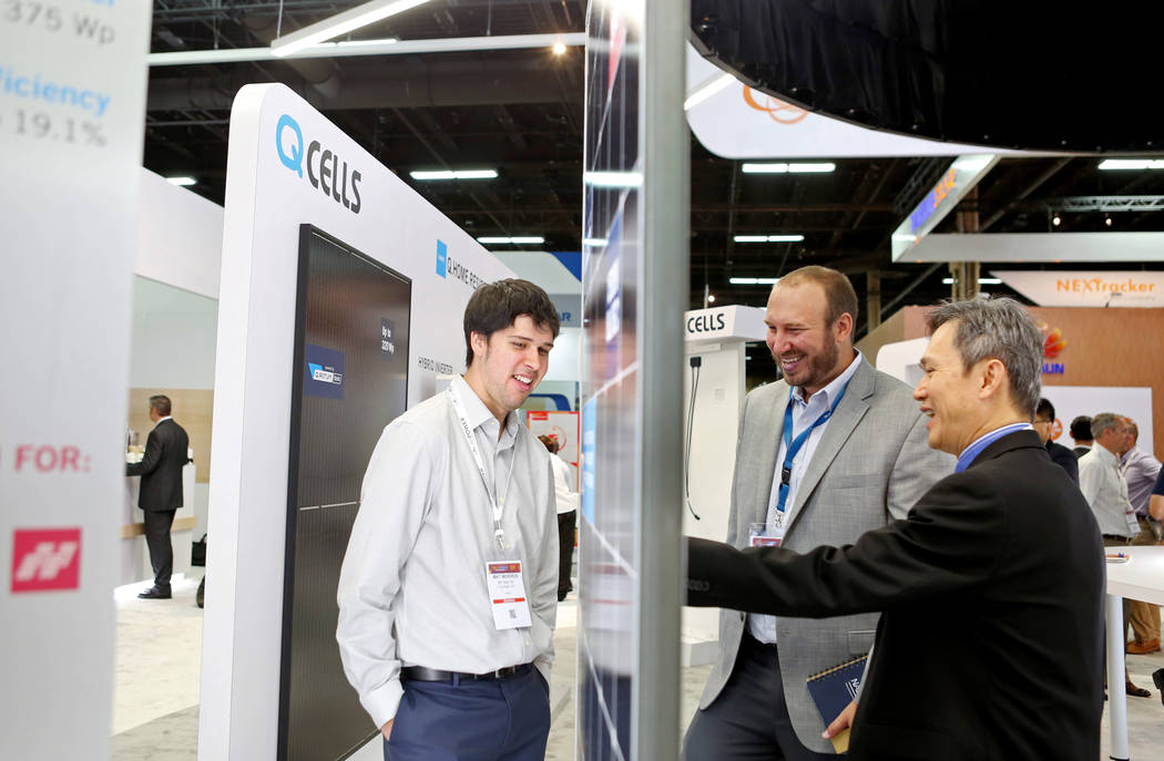 RBI Solar Mountain System's Mat Mideros' estimator Mat Mideros, left, and RBI Solar's director of codes and standards James Cormican, center, speak with Hanwha Q Cell's senior director of products ...