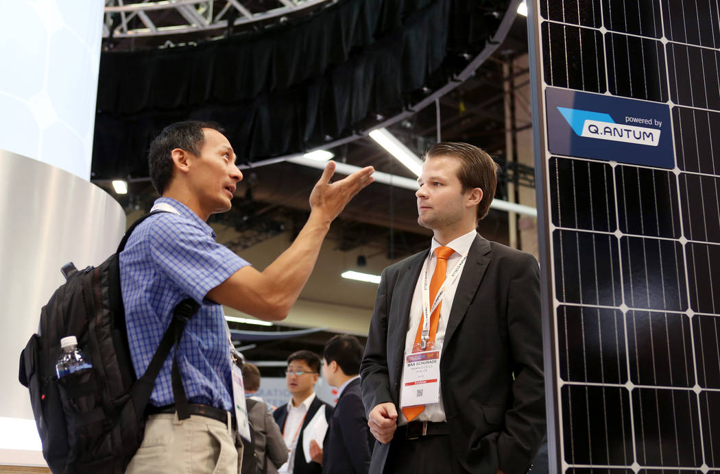 Vu Lac with TE Connectivity, left, and Max Schurad with Hannah Q Cells during the Solar Power International 2017 at the Mandalay Bay Convention Center in Las Vegas, Monday, Sept. 11, 2017. (Elizab ...