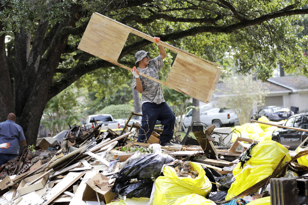 Rene Ramirez helps move debris from a home damaged by floodwaters in the aftermath of Hurricane Harvey on Wednesday, Sept. 6, 2017, in Spring, Texas. (AP Photo/David J. Phillip)